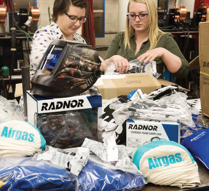 Ferris welding engineering technology students Kate Wernecke (left) and Bobbi Jo Matheny (right) sort through welding supplies donated to the school by Airgas, Inc.